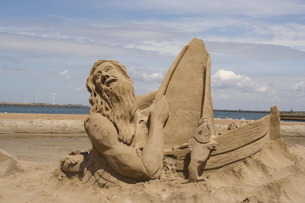Sand Sculpture on a Beach of a Sailor in a Boat Taking on Water