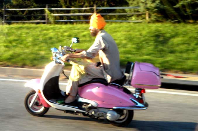 Photo of a Muslim Man in Tan Robes and Bright orange hat driving a pink barbie scooter. Photo By Kelly A. Harmon