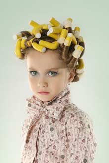 A very young girl in curlers and make up.