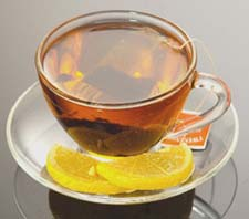 Tea in a clear teacup with a slice of lemon on the side.
