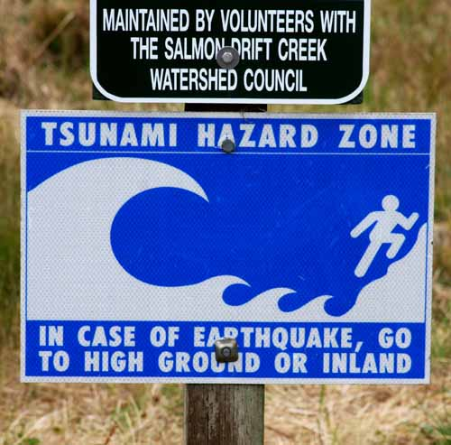 Photograph of a sign which reads: Tsunami Hazard Zone: In case of earthquake, go to high ground or inland.