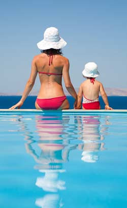 Mommy and baby girl in bikinis with their backs to the camera, sitting on the edge of a pool.
