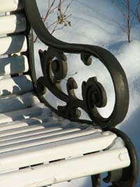 Park bench with wrought -iron handles on a snowy day.