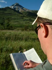 Man reading a book outside with a mountain view in the distance.