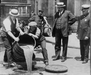 New York City Deputy Police Commissioner John A. Leach (right) watches as Prohibition agents pour illegal liquor into a sewer in 1921.